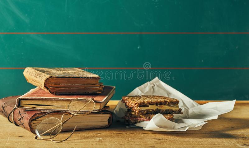 Nostalgic vintage still life of school lunch break. Nostalgic vintage still life of a school lunch break with old leather bound books, metal rimmed reading royalty free stock photos