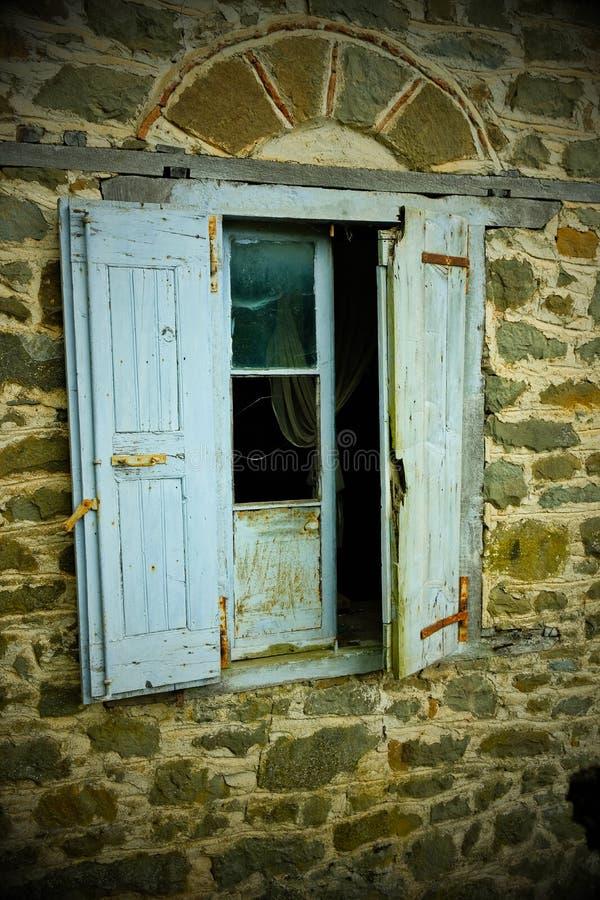 Nostalgisk karaktärsteckning, bleknade blåa fönsterslutare på det övergav huset, Grekland fotografering för bildbyråer