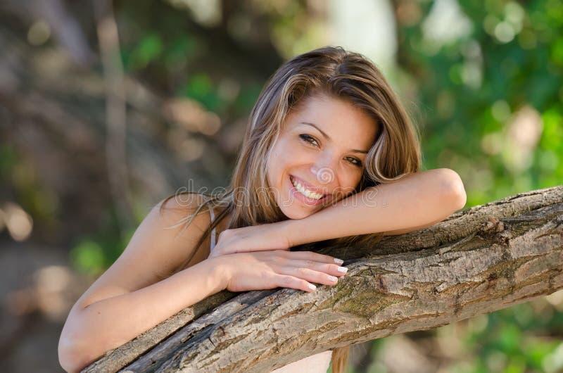 Nostalgiska ögonblick av en härlig flicka, som hon vilar på en trädstam fotografering för bildbyråer
