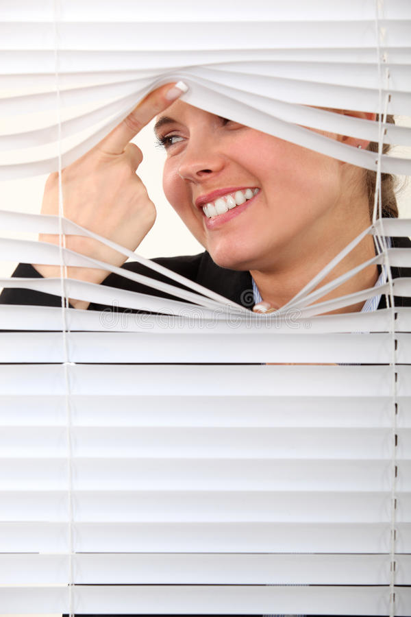 Nosy woman. Peering through some blinds stock images