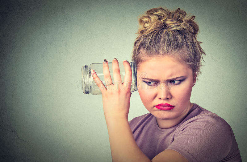 Nosy woman with glass jar listens to gossip behind the wall royalty free stock photography