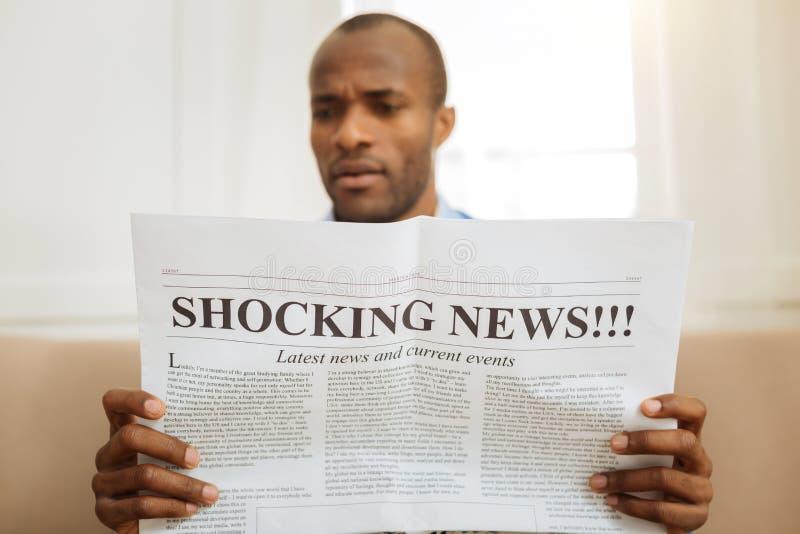 Notícia chocante de leitura desconcertada do homem imagens de stock royalty free