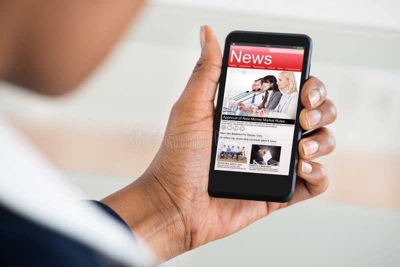 Notícia da leitura da mulher no telefone celular fotos de stock