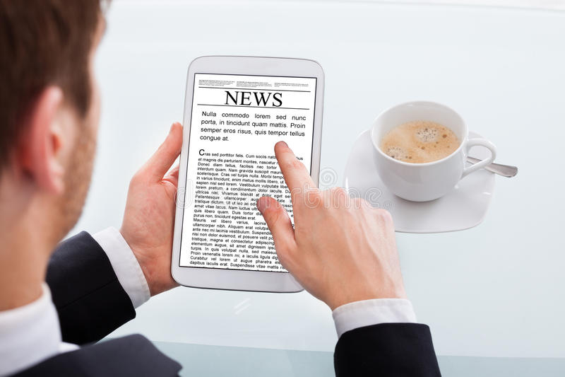 Notícia da leitura do homem de negócios na tabuleta digital na mesa fotografia de stock