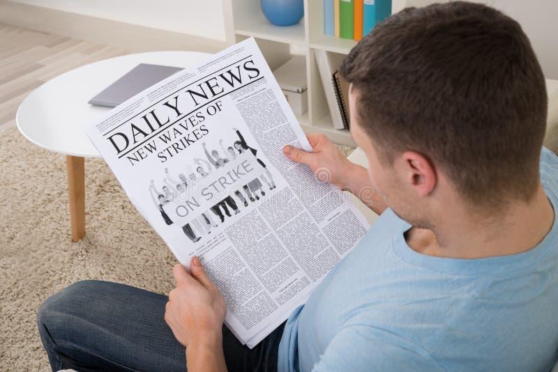Notícia da leitura do homem no jornal em casa fotografia de stock