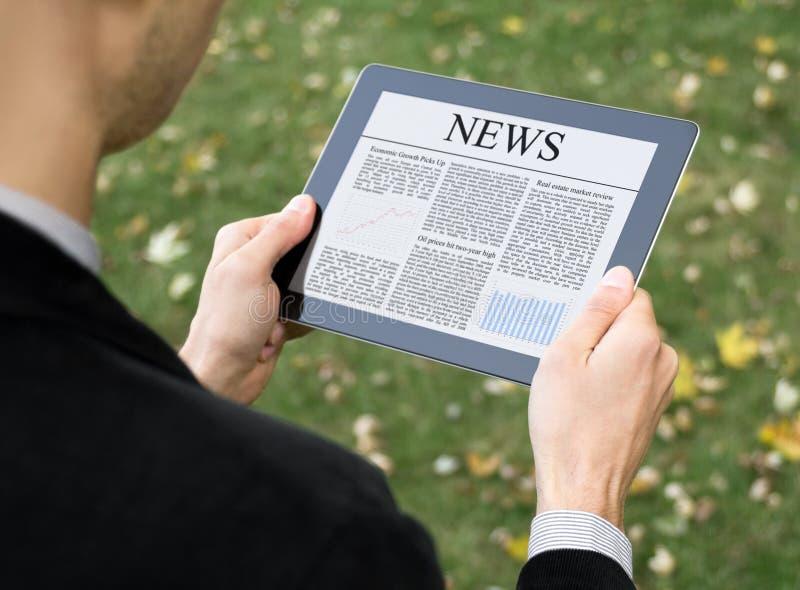 Notícia da leitura no PC da tabuleta imagem de stock