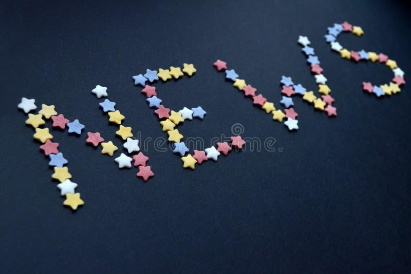 A notícia da palavra é escrita pelo tipo fino de estrelas da pastelaria do açúcar em um fundo azul, anunciando, comércio, vendas imagens de stock royalty free