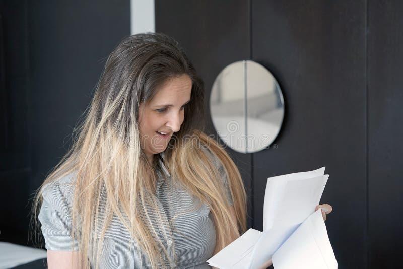Notícia de leitura da mulher feliz do empresário boa em uma letra no sofá fotos de stock royalty free
