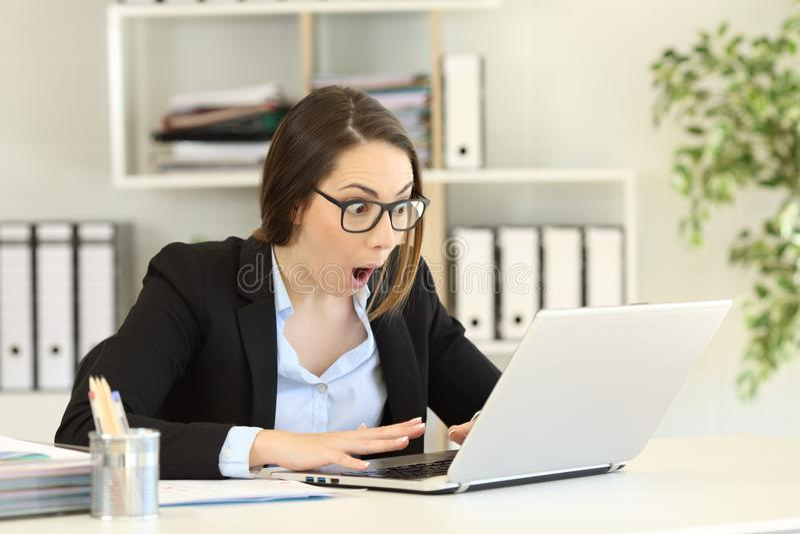 Notícia de leitura surpreendida de trabalhador de escritório boa em um computador fotos de stock