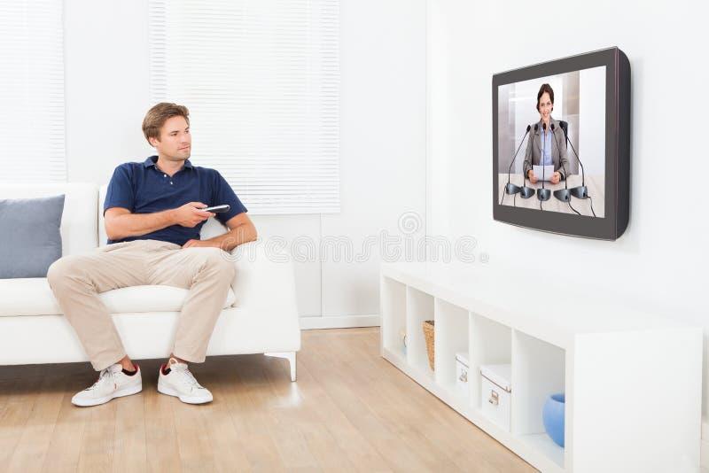 Notícia de observação do homem na tevê em casa fotografia de stock
