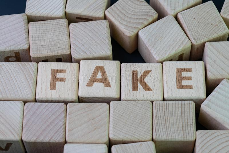 Notícia falsificada ou conceito falso da informação, bloco de madeira do cubo com liga do alfabeto a falsificação da palavra no f imagens de stock royalty free