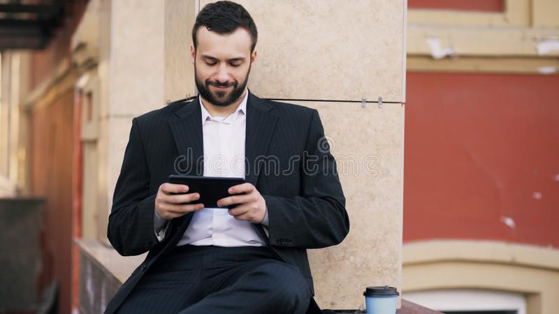 Notícia farpada nova da leitura do homem de negócios no tablet pc e no café da bebida durante a ruptura perto de seu prédio de es imagens de stock