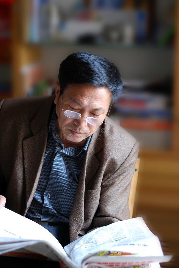 Notícia madura asiática da leitura do homem fotografia de stock royalty free