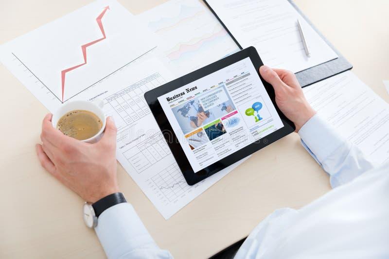 Notícia a mais atrasada de leitura do homem de negócios no ipad da maçã imagens de stock royalty free