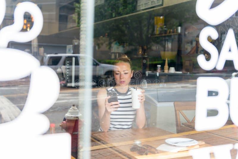 Notícia pensativa da leitura da mulher no telefone celular durante o resto na cafetaria imagens de stock royalty free