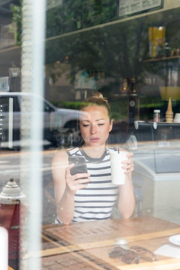 Notícia pensativa da leitura da mulher no telefone celular durante o resto na cafetaria imagens de stock