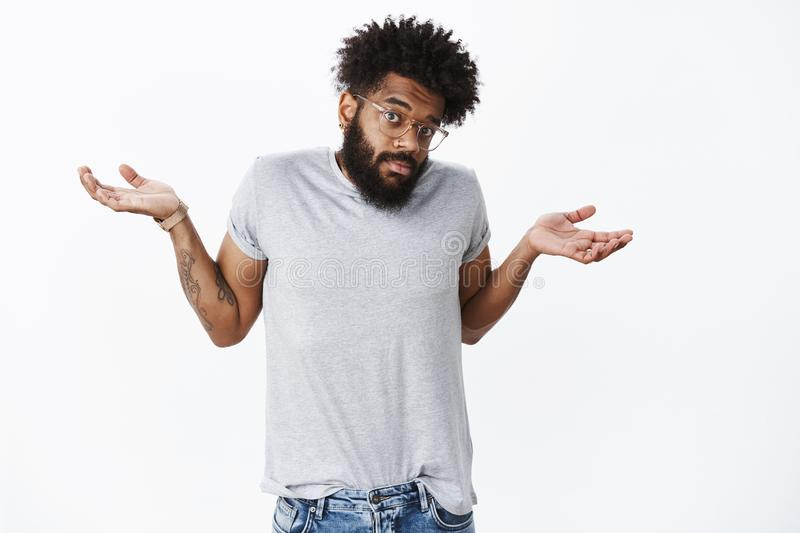 So, not big deal. Portrait of confused and questioned unaware funny african american man shrugging with puzzled look and. Hands raised sideways, having no idea stock photography