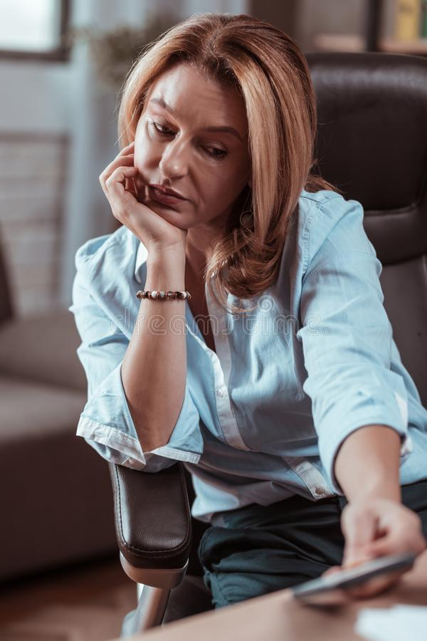 Blonde-haired wife feeling sad not getting call from her husband. Not getting call. Blonde-haired appealing stylish wife feeling sad not getting call from her royalty free stock images