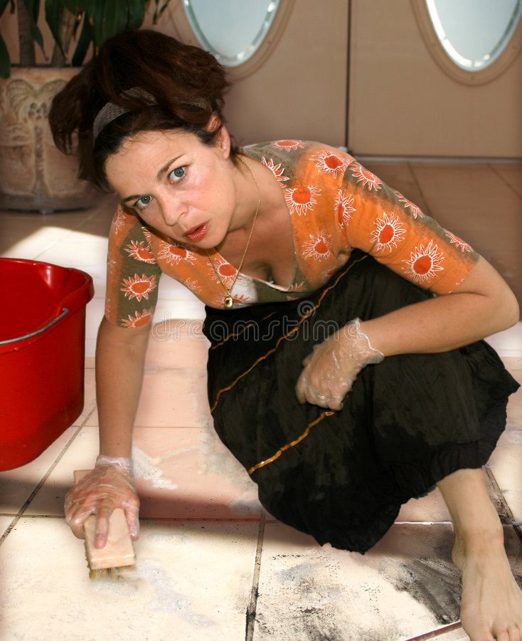 Not so happy housewife. Middle aged woman looking unhappy while scrubbing a dirty floor royalty free stock photography