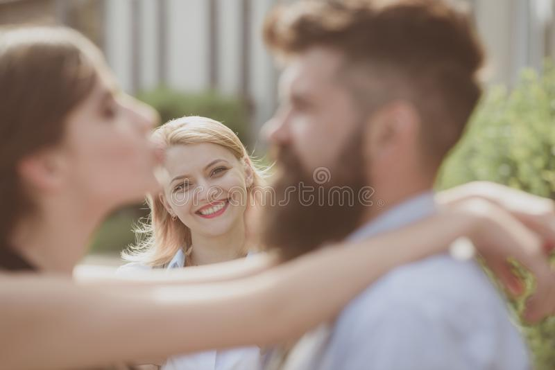 She is not jealous. Bearded man cheating his girlfriend with another woman. Romantic couple of man and woman dating stock photos