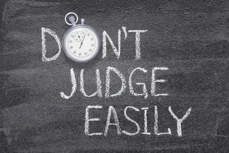 Not judge easily. Do not judge easily phrase written on chalkboard with vintage precise stopwatch stock images