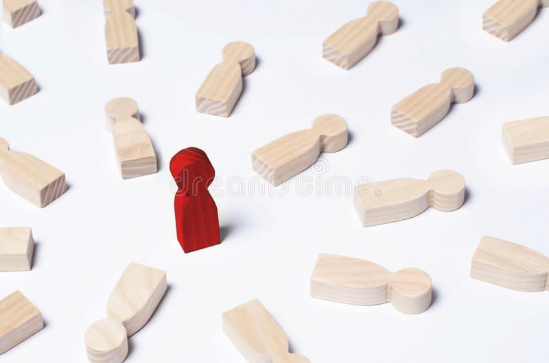 Not like everyone else. The red man stands in the middle of lying opponents. The concept of excellence, business success. An outcast, a schismatic, a bad royalty free stock images