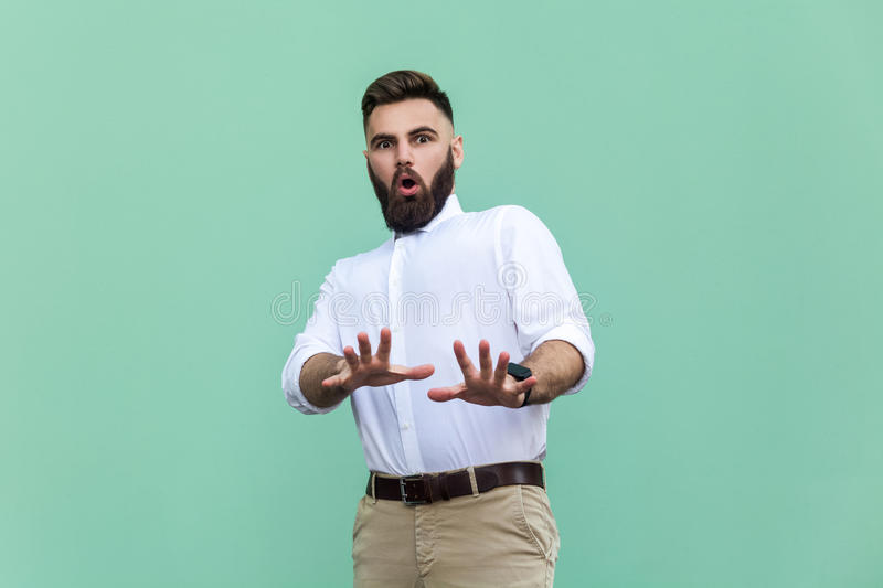 Not me! Stylish bearded man with shocked. Businessman having amazed face, looking at camera. Indoor, studio shot, light green background royalty free stock photography