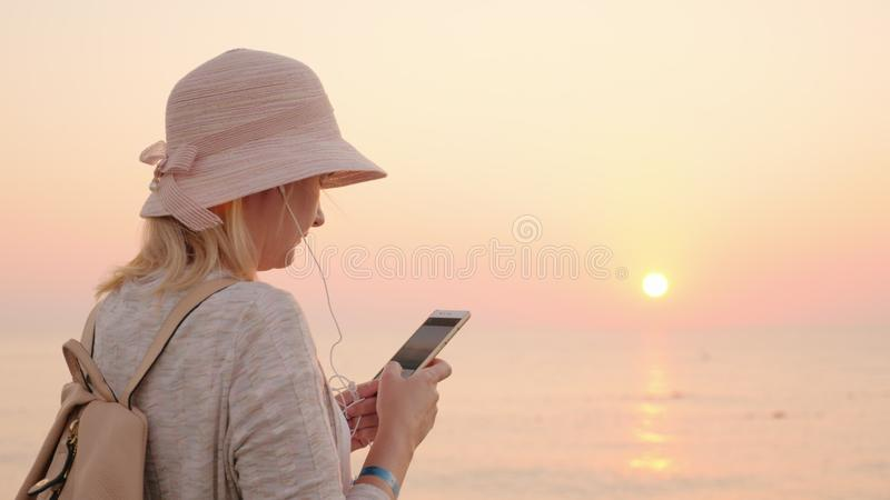 Not a minute without a phone, the girl is standing on the beach with a pink sky and sky, looking at the phone screen and stock images