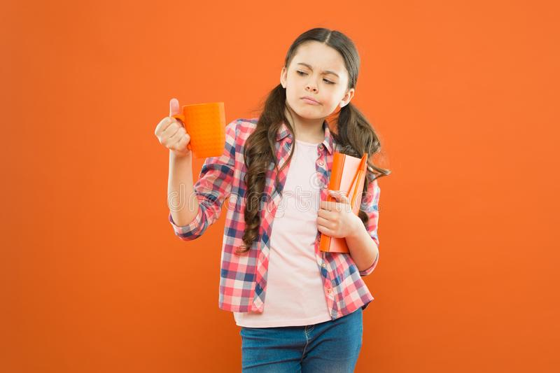 This is not my cup of tea. Dissatisfied girl looking at cup during lunch on orange background. School child having lunch stock image