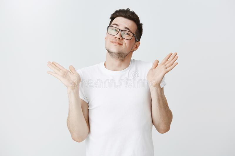 Not my deal, I do not care. Portrait of man sweep arms with open palms near shoulders smiling awkward with careless look. Making shrug, standing unbothered and royalty free stock photography