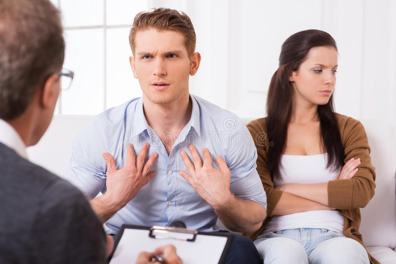 It is not my fault!. Displeased young men talking to psychiatrist and gesturing while his wife sitting near him and keeping arms crossed stock photo