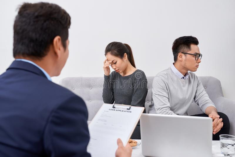 It is not my fault! Displeased young man talking to psychiatrist and gesturing while his wife sitting near him and keeping arms royalty free stock photo
