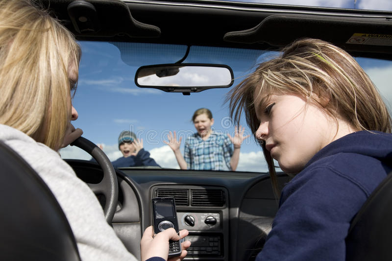 Not paying attention texting accident. Two teenagers being distracted by a cell phone text, instead of watching the road. They are about to hit a boy and girl royalty free stock photo