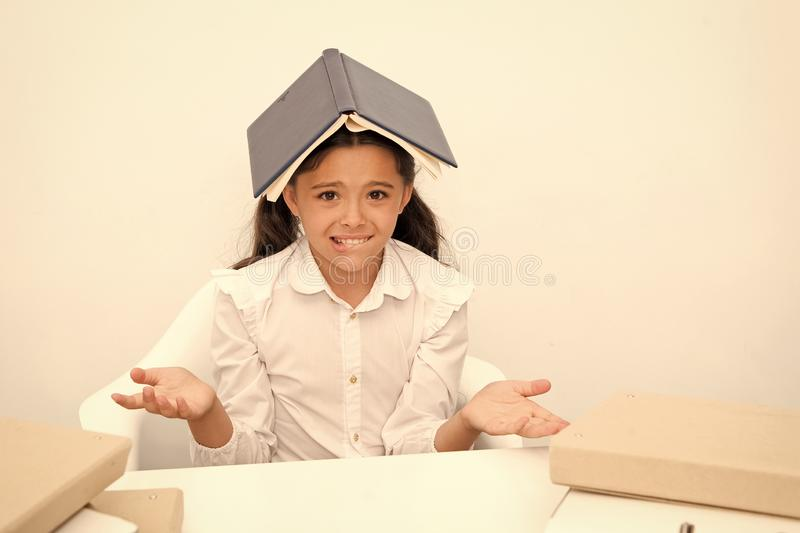 Not possible to remember. Girl child confused exhausted book roof head white background. Schoolgirl tired of tries to stock image
