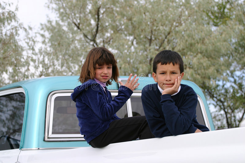 Not and Serious. Two Latin American kids in the back of an old pick up truck. The young girl not serious while the young boy is very intent. If you like this royalty free stock photography
