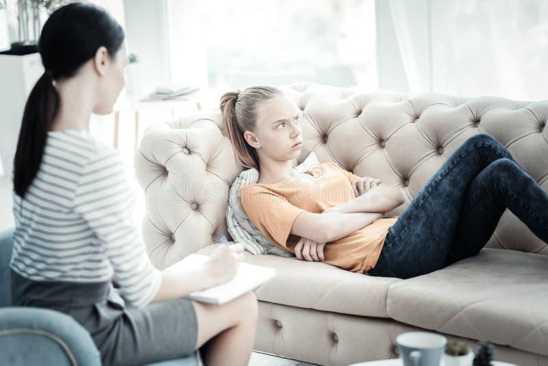 Upset teen girl refusing to talk with psychologist stock photos