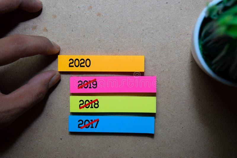 Nota adhesiva Man Pulling 2020 sobre fondo de mesa de madera Feliz Año Nuevo fotos de archivo