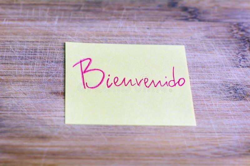 Nota amarilla con el mensaje agradable en español - bienvenido imagen de archivo libre de regalías