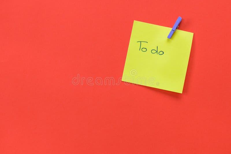 Nota amarilla con el texto a hacer aislado en un fondo rojo imagen de archivo