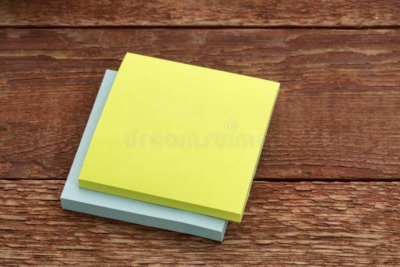 Nota appiccicosa in bianco contro legno fotografia stock