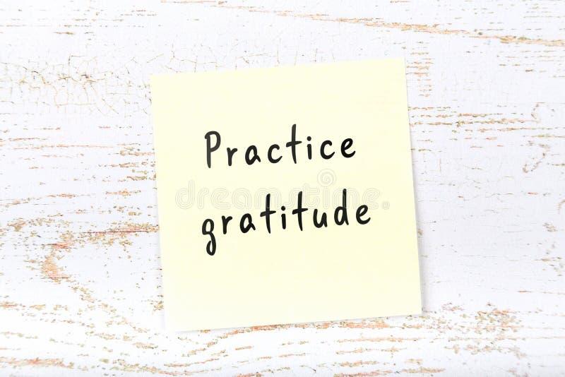 Nota appiccicosa gialla sullo scrittorio di legno con ringraziamento scritto a mano di pratica del testo fotografie stock