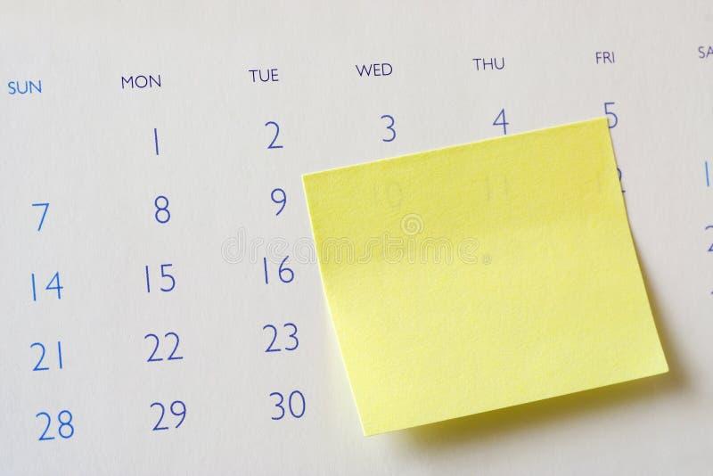 Nota appiccicosa sul calendario fotografie stock