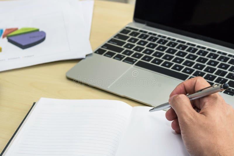 Nota da escrita do homem de negócios no caderno e no portátil do uso imagens de stock