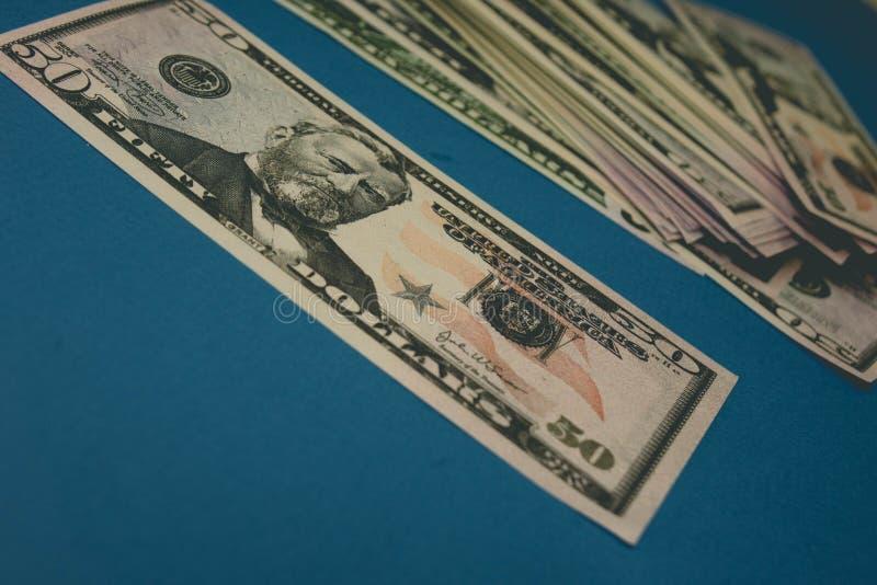 Nota de d?lar cinq??nta em um fundo azul que est? sendo estudado atrav?s de uma lupa imagens de stock royalty free