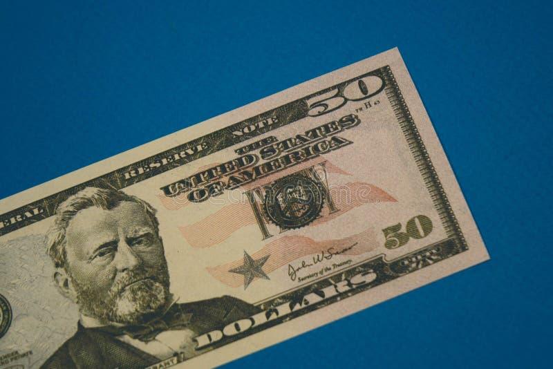 Nota de d?lar isolada do americano cinq??nta no fundo azul fotografia de stock
