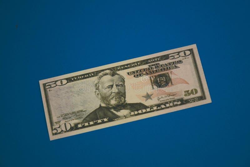 Nota de d?lar isolada do americano cinq??nta no fundo azul imagem de stock royalty free