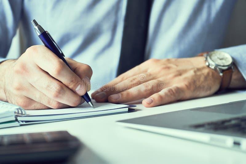 Nota de la escritura de la mano del hombre de negocios sobre un cuaderno Hombre de negocios que trabaja en el escritorio de ofici foto de archivo libre de regalías