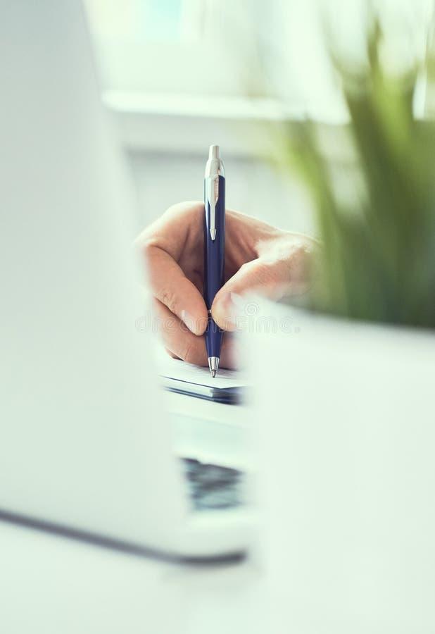 Nota de la escritura de la mano del hombre de negocios sobre un cuaderno Hombre de negocios que trabaja en el escritorio de ofici imágenes de archivo libres de regalías