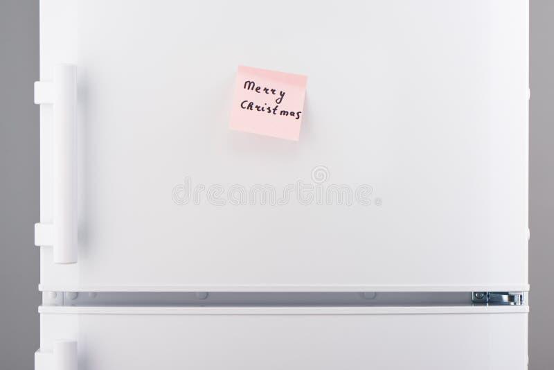 Nota de la Feliz Navidad sobre el documento pegajoso rosado sobre el refrigerador blanco fotografía de archivo
