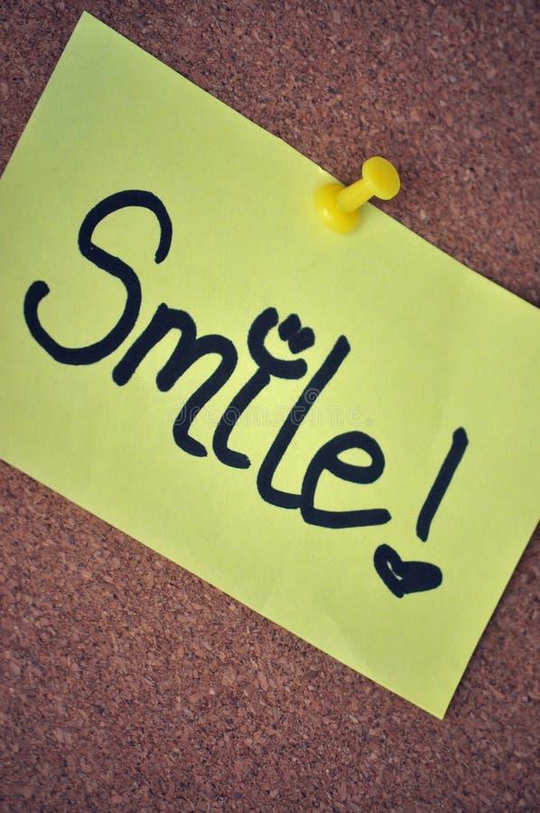 Nota De La Sonrisa Sobre Tablón De Anuncios Imagen de archivo libre de regalías